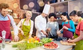 Les amis et le chef heureux font cuire la cuisson dans la cuisine Images stock