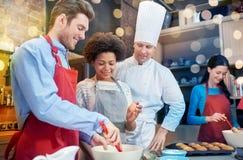 Les amis et le chef heureux font cuire la cuisson dans la cuisine Photos libres de droits