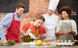 Les amis et le chef heureux font cuire la cuisson dans la cuisine Image stock