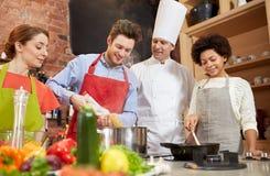 Les amis et le chef heureux font cuire la cuisson dans la cuisine Photographie stock libre de droits