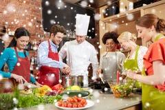 Les amis et le chef heureux font cuire la cuisson dans la cuisine Photo stock