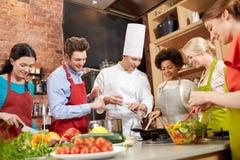 Les amis et le chef heureux font cuire la cuisson dans la cuisine Photographie stock