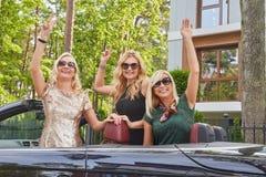 Les amis féminins à la mode joyeux soulèvent leurs mains tout en se reposant dans la voiture de luxe de cabriolet en parc Images libres de droits