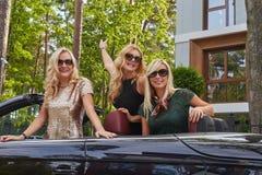 Les amis féminins à la mode joyeux soulèvent leurs mains tout en se reposant dans la voiture de luxe de cabriolet en parc Photo stock