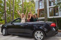 Les amis féminins à la mode joyeux soulèvent leurs mains tout en se reposant dans la voiture de luxe de cabriolet en parc Photos libres de droits