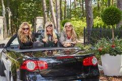 Les amis féminins à la mode joyeux soulèvent leurs mains tout en se reposant dans la voiture de luxe de cabriolet en parc Image libre de droits