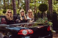 Les amis féminins à la mode joyeux soulèvent leurs mains tout en se reposant dans la voiture de luxe de cabriolet en parc Images stock