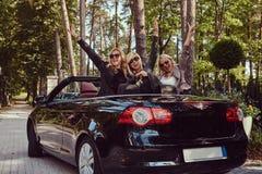 Les amis féminins à la mode joyeux soulèvent leurs mains tout en se reposant dans la voiture de luxe de cabriolet en parc Photographie stock libre de droits