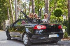 Les amis féminins à la mode joyeux soulèvent leurs mains tout en se reposant dans la voiture de luxe de cabriolet en parc Photo libre de droits