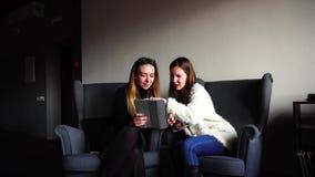 Les amis féminins élégants utilisent le comprimé et communiquent parmi eux-mêmes pendant le dîner et s'asseyent dans les chaises  banque de vidéos