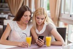Les amis féminins assez jeunes utilisent le téléphone dedans Images libres de droits