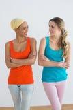 Les amis féminins avec des bras ont croisé dans la nouvelle maison Images stock
