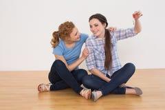 Les amis féminins avec la maison verrouille se reposer sur le plancher Photographie stock libre de droits