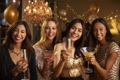 Les amis féminins célébrant à la partie font le pain grillé à l'appareil-photo Photographie stock