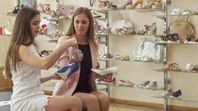 Les amis féminins choisissent entre trois chaussures à la boutique banque de vidéos