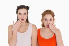 Les amis féminins choqués avec remettent la bouche Images stock