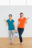 Les amis féminins de sourire avec des brosses et la peinture peuvent dans la nouvelle maison Photos libres de droits