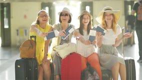 Les amis féminins de sourire sont très heureux d'aller aux vacances d'été ensemble Quatre filles attendent leur avion avec clips vidéos