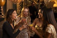 Les amis féminins font le pain grillé pendant qu'ils célèbrent à la partie Photo stock