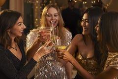 Les amis féminins font le pain grillé pendant qu'ils célèbrent à la partie Photo libre de droits
