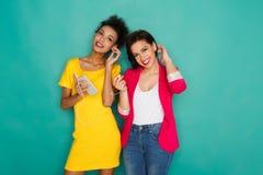 Les amis féminins heureux écoutent la musique au fond de studio Photo libre de droits