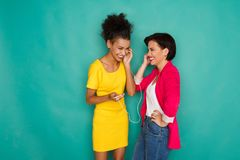 Les amis féminins heureux écoutent la musique au fond de studio Photo stock
