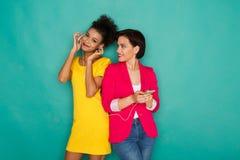 Les amis féminins heureux écoutent la musique au fond de studio Images stock