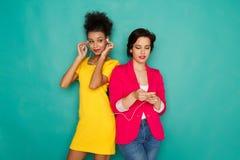 Les amis féminins heureux écoutent la musique au fond de studio Photos stock