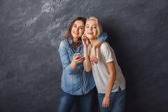 Les amis féminins heureux écoutent la musique au fond de studio Photos libres de droits