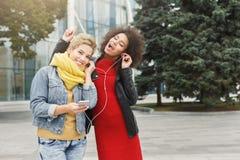 Les amis féminins heureux écoutent la musique dehors Images stock