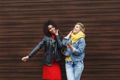 Les amis féminins heureux écoutent la musique dehors Photos libres de droits