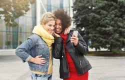 Les amis féminins heureux écoutent la musique dehors Image stock