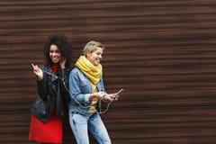 Les amis féminins heureux écoutent la musique dehors Photo stock