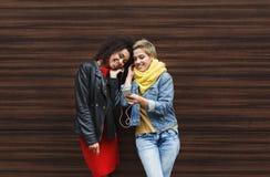 Les amis féminins heureux écoutent la musique dehors Image libre de droits