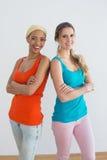 Les amis féminins heureux avec des bras ont croisé dans la nouvelle maison Images stock