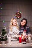 Les amis féminins heureux jouant dans Noël ont décoré l'intérieur Image libre de droits