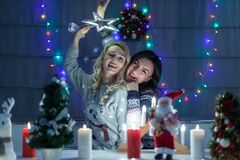 Les amis féminins heureux jouant dans Noël ont décoré l'intérieur Photo stock
