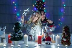 Les amis féminins heureux jouant dans Noël ont décoré l'intérieur Images libres de droits