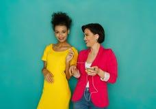 Les amis féminins joyeux écoutent la musique au fond de studio Images stock