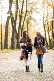 Les amis féminins multiraciaux marchant pendant l'automne se garent Photographie stock