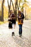 Les amis féminins multiraciaux marchant pendant l'automne se garent Photo stock