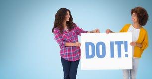 Les amis féminins tenant le panneau d'affichage avec il textotent sur le fond bleu Photo stock