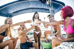 Les amis faisant des poissons grillent tout entier sur le yacht Images libres de droits