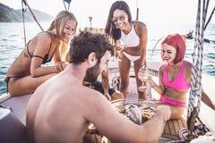 Les amis faisant des poissons grillent tout entier sur le yacht Photos stock