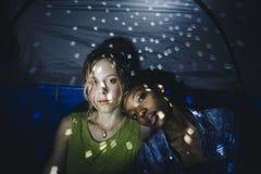 Les amis faisant la fête dans une nuit s'allument dans la tente Photos stock