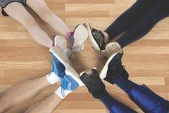 Les amis font le cercle de pied sur le plancher Images stock