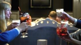 Les amis font tinter des verres avec des cocktails tout en célébrant quelque chose tout en se reposant dans un restaurant d'élite banque de vidéos