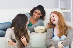 Les amis gais avec à télécommande et le maïs éclaté roulent à la maison Photographie stock