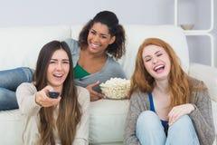 Les amis gais avec à télécommande et le maïs éclaté roulent à la maison Photographie stock libre de droits
