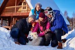 Les amis gais avec le chien passent des vacances d'hiver ensemble au cottage de montagne Photos libres de droits